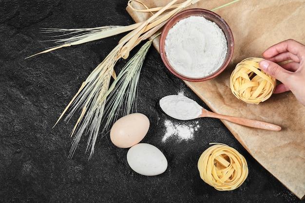 Ciotola di farina, uova crude, tagliatelle secche e cucchiaio di legno sul tavolo scuro.