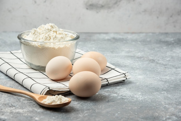 Bowl of flour and raw eggs on tablecloth.