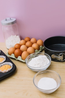 Bowl of flour; sugar; eggs; cupcake and baking tin on wooden desk against pink background