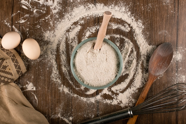 Bowl of flour with eggs and and wooden spoon