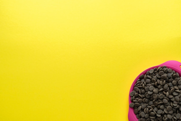 A bowl of food on a yellow background in the lower right corner. flat lay, top view. space for text.