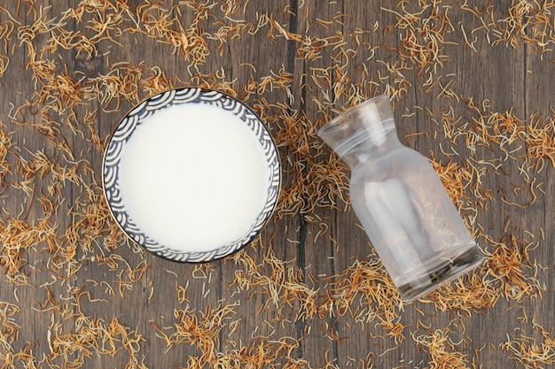 A bowl of fresh cool milk with an empty glass pitcher placed on wooden table