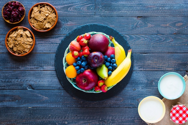 Bowl of fresh fruit with banana, apple, strawberries, apricots, blueberries, plums, whole grains, forks, top view