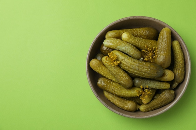 Bowl of fresh pickles on green background