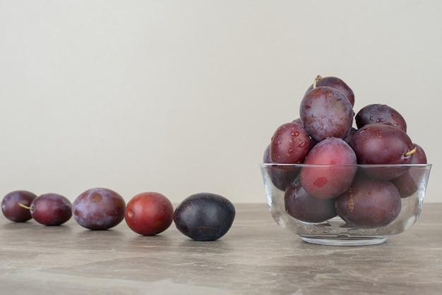 Ciotola di prugne fresche sulla tavola di marmo.