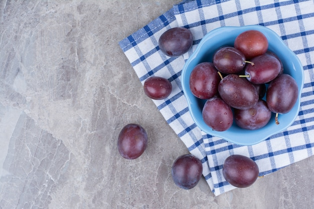 Bowl of fresh plums on stone background with tablecloth.