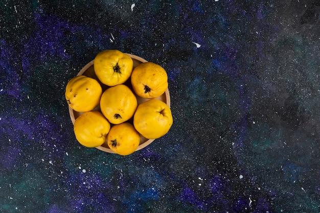 Ciotola di mele cotogne fresche poste sul tavolo scuro.