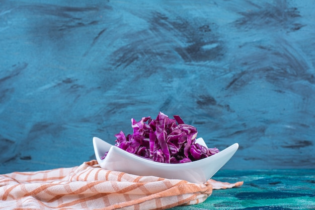 A bowl of fresh red cabbage on a tea towel