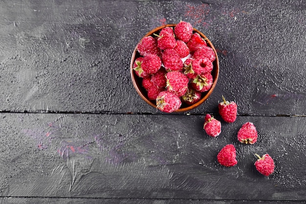 Bowl of fresh red raspberries on dark wooden table.