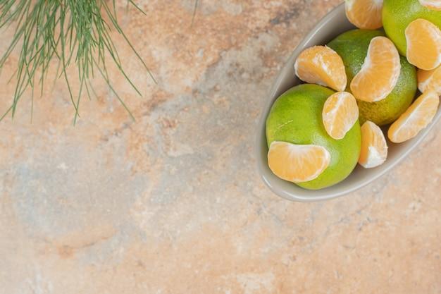 Bowl of fresh tangerine and segments on marble background.