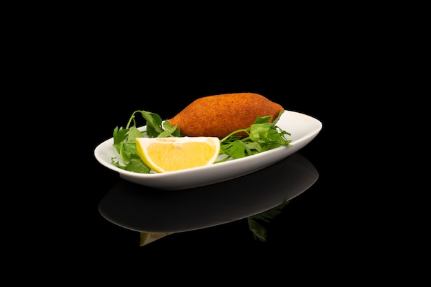 Bowl of fried stuffed meatballs inside it nuts and minced meat with lemon and green vegetable