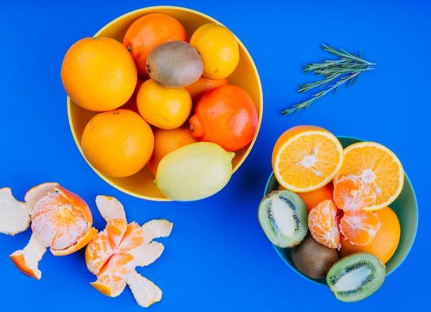 Bowl of fruit lemon; orange fruit and kiwi against blue background