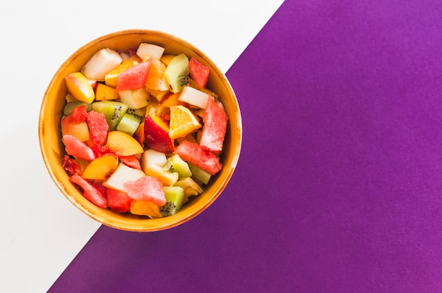Bowl of fruit salad on white and purple background