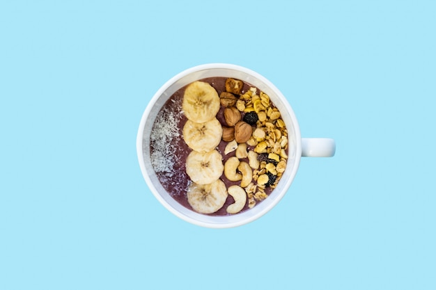 Bowl of fruit smoothie with nuts and banana, top view. flat lay of an acai bowl with cereals, cashews and hazelnuts in blue bright surface