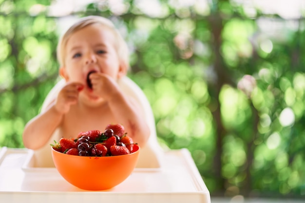 Bowl of fruit on a table on the balcony in front of a eating child