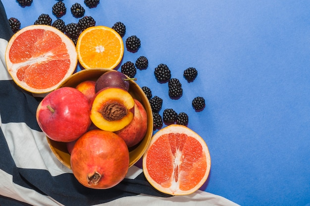 Bowl of fruits; citrus fruit and black berries on blue background