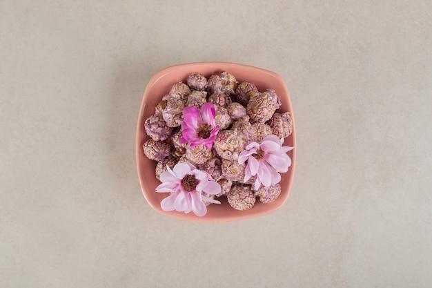 Ciotola piena di popcorn ricoperto di caramelle sormontato da fiori su marmo.