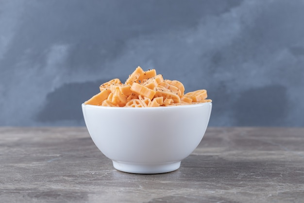 Bowl full of different shaped pasta , on the marble surface.