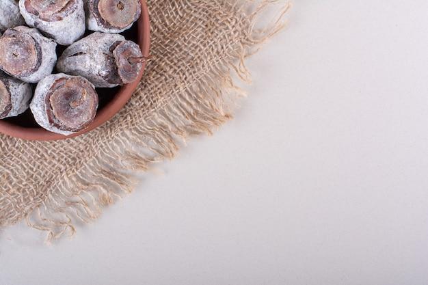 Ciotola piena di cachi secchi e tela ruvida su sfondo bianco. foto di alta qualità