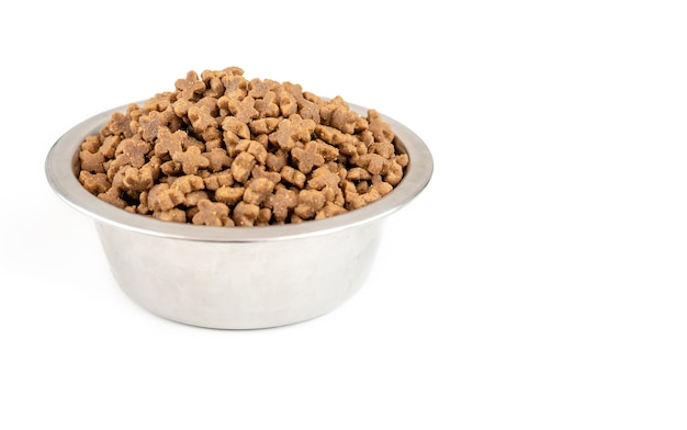 Bowl full of dry pet food isolated on white surface, side viev
