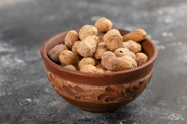 Bowl full of healthy peanuts in shell placed on a stone table .