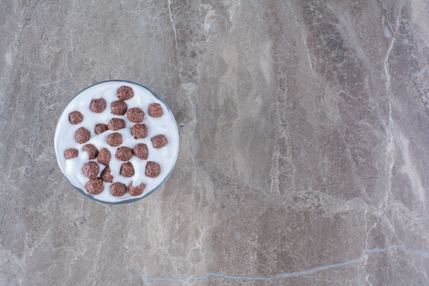 A bowl full of healthy yogurt and small chocolate cereal balls .