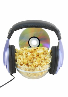Чаша, полная карамельного попкорна, dvd-диск и наушники. изолированные