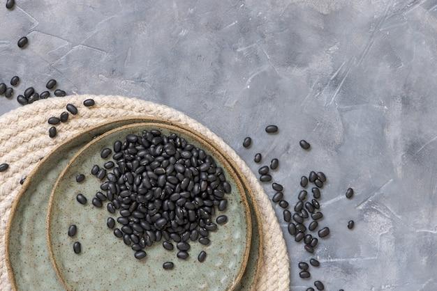 Чаша, полная сушеных черных бобов на сером столе с копией пространства. здоровое питание и вегетарианская концепция. традиционный латиноамериканский кузен ингредиент