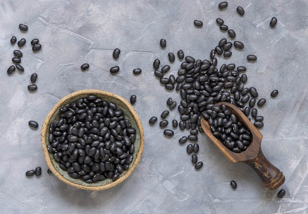 나무 국자와 말린 검은 콩으로 가득 찬 그릇