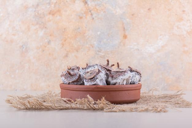 말린 감과 흰색 배경에 삼베로 가득 찬 그릇. 고품질 사진