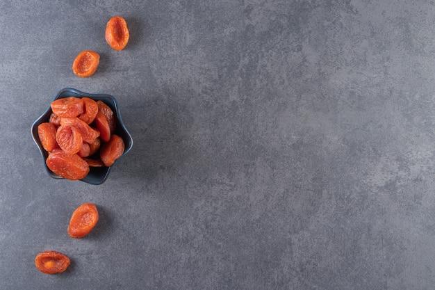 Чаша, полная здоровых сушеных плодов абрикоса на каменном фоне.