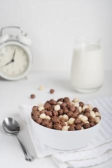 바로 먹을 수있는 건강한 채식 시리얼이 공 모양으로 가득 찬 그릇에 우유 한 잔 제공