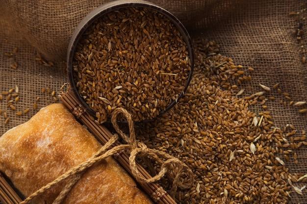 빵 한 덩어리와 함께 자루에 호밀의 전체 그릇. 다이어트를 위한 건강한 유기농 성분.