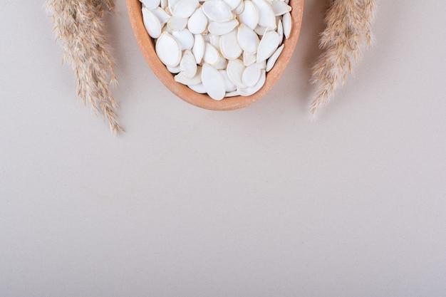 Ciotola piena di semi di zucca organici su sfondo bianco. foto di alta qualità