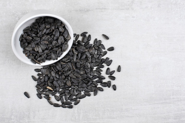 Bowl full of sunflower black seeds placed on stone table .