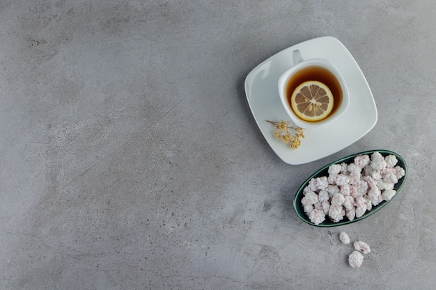 A bowl full of sweet white candies with a glass cup of hot tea on a stone table .