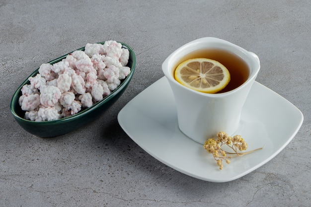 A bowl full of sweet white candies with a glass cup of hot tea on a stone