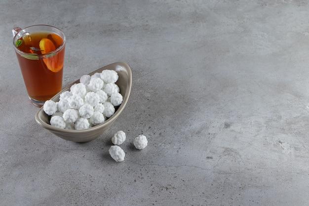 Una ciotola piena di dolci caramelle bianche con una tazza di vetro di tè caldo su una pietra