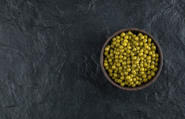 Ciotola piena di piselli verdi marinati sul tavolo nero.