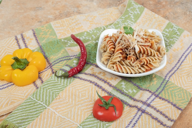 Bowl of fusilli pasta and fresh vegetables on tablecloth