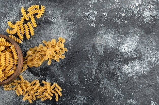 Bowl of fusilli pasta on marble surface