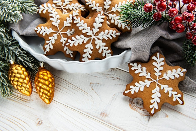 Bowl of gingerbread christmas cookies on rustic white wooden table, and green fir branch. copy space.
