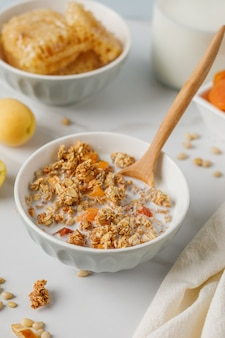 Bowl of granola with dried apricot on white marble table. wooden spoon.