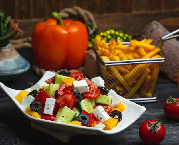 Bowl of greek salad garnished with yellow bell pepper, served with fries