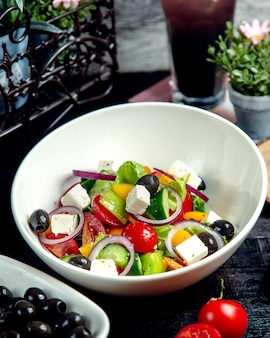 A bowl of greek salad with cucumber tomato yellow pepper red onion olive and white cheese