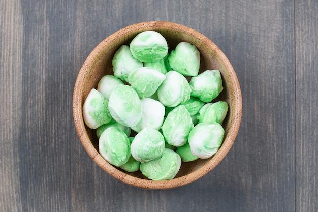 Ciotola di caramelle verdi su superficie di legno