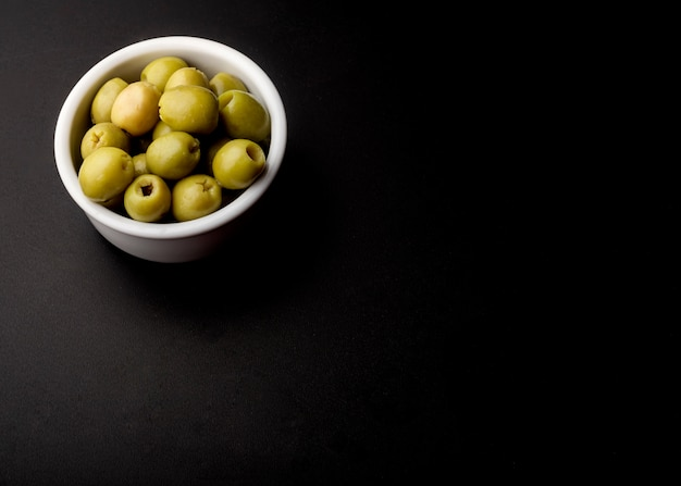 Bowl of green fresh olive over black backdrop