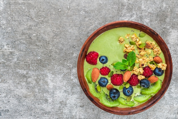 Bowl of green matcha tea smoothie with fresh berries, fruits, granola, nuts and seeds for healthy vegan breakfast