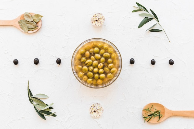 Bowl of green olives decorated with herbs and garlic bulbs