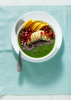 Bowl of green smoothie with sliced mango, banana, pomegranate seeds and chia seeds, maple syrup for a healthy morning breakfast
